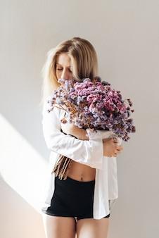Portret pięknej młodej dziewczyny w białej koszuli, czarnej bluzce i szortach, trzymającej duży bukiet suszonych kwiatów na szaro