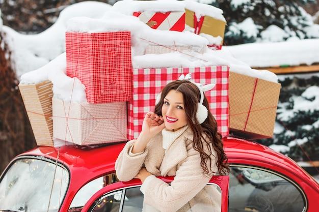 Portret pięknej młodej dziewczyny, wesołej i szczęśliwej w czerwonym samochodzie z prezentami