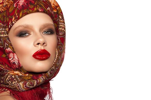 Portret pięknej młodej dziewczyny z chustą na głowie, jasny makijaż i czerwone usta, białe tło.