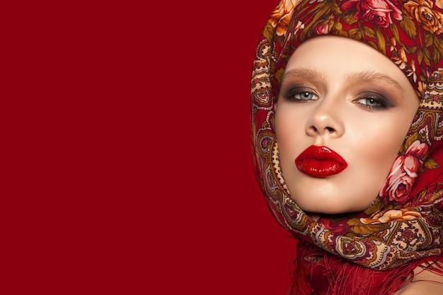 Portret pięknej młodej dziewczyny z chustą na głowie, jasny makijaż i czerwone usta, czerwone tło.