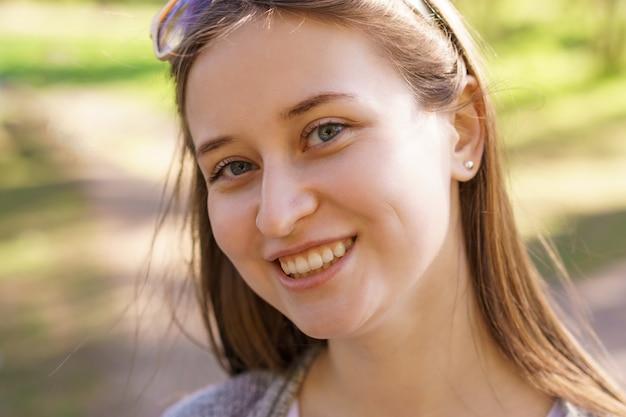 Portret pięknej młodej dziewczyny z kolczykiem w uchu, która uśmiecha się do kamery w słoneczny dzień