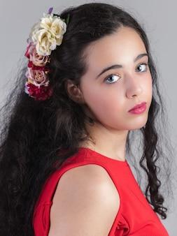 Portret pięknej młodej dziewczyny z kwiatem we włosach.