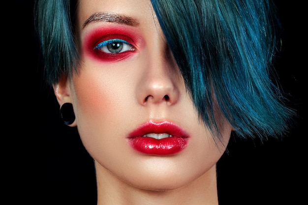 Portret pięknej młodej dziewczyny z profesjonalnym makijażem, dziwadło. punkowa dziewczyna o niebieskich oczach, czerwonych ustach i niebieskich, zielonych foliosach