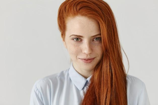 Portret pięknej młodej europejskiej studentki z piegami w jej długich rudych włosach