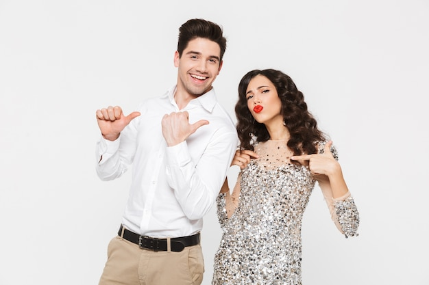 Portret pięknej młodej inteligentnej ubranej pary stojącej na białym tle nad białym, obchodzi nowy rok, wskazując palcami na siebie