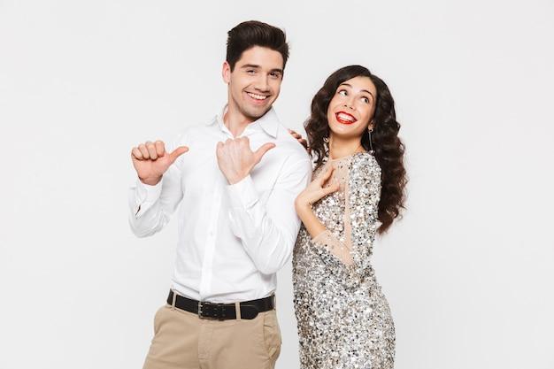 Portret pięknej młodej inteligentnej ubranej pary stojącej na białym tle nad białym, świętuje nowy rok, wskazując palcami