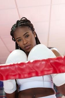 Portret pięknej młodej kobiety afro american patrząc na kamery w rękawicach bokserskich wewnątrz ringu w siłowni.