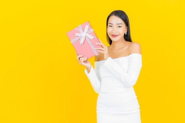 Portret pięknej młodej kobiety asian biznesu z czerwonym pudełkiem na żółtej ścianie