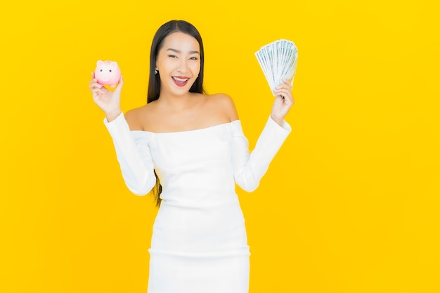 Portret pięknej młodej kobiety asian biznesu z dużą ilością gotówki i skarbonki na żółtej ścianie