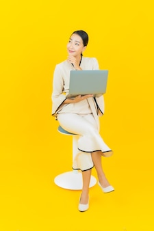 Portret pięknej młodej kobiety asian biznesu z komputera laptop na żółtej ścianie