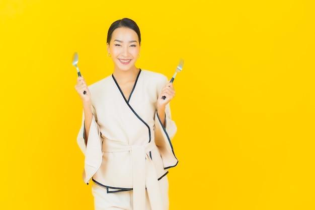 Portret pięknej młodej kobiety asian biznesu z łyżką i widelcem gotowe do spożycia na żółtej ścianie