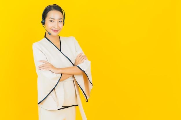 Portret pięknej młodej kobiety asian biznesu z zestawem słuchawkowym do obsługi klienta call center na żółtej ścianie