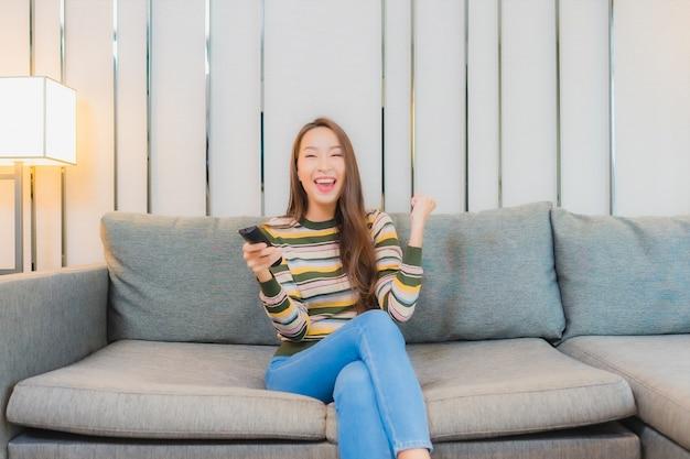 Portret pięknej młodej kobiety asian używać pilota do telewizora na kanapie we wnętrzu salonu