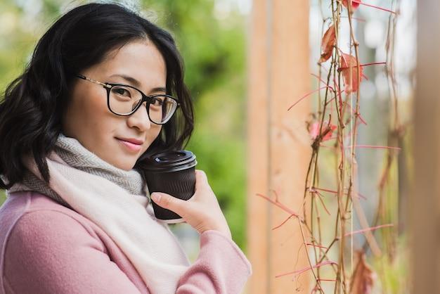Portret pięknej młodej kobiety azjatki picia gorącego napoju z jednorazowego kubka papierowego na zewnątrz. dziewczyna w okularach patrzy w kamerę.