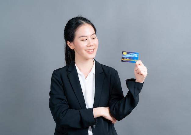 Portret pięknej młodej kobiety azjatyckich w szmatki oficera przedstawiające kartę kredytową z miejsca na kopię na szarej ścianie