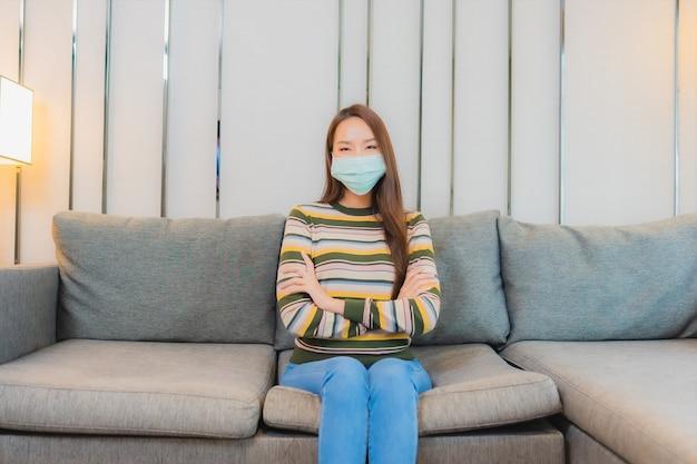 Portret pięknej młodej kobiety azjatyckie nosi maskę na kanapie we wnętrzu salonu