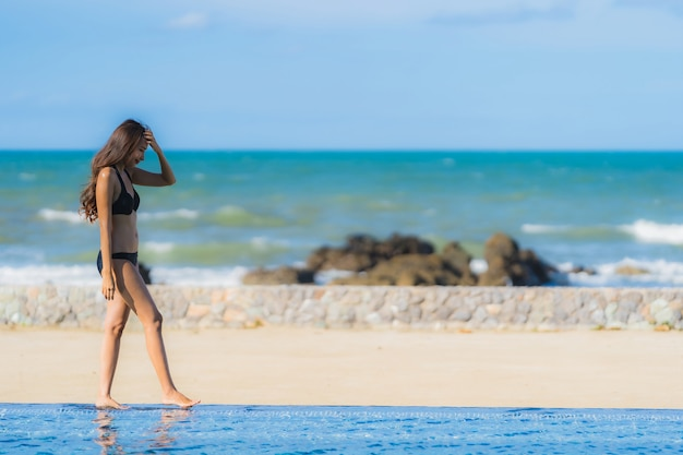 Portret pięknej młodej kobiety azjatyckie nosić bikini wokół basenu w hotelowym kurorcie prawie oceanu morza plaży