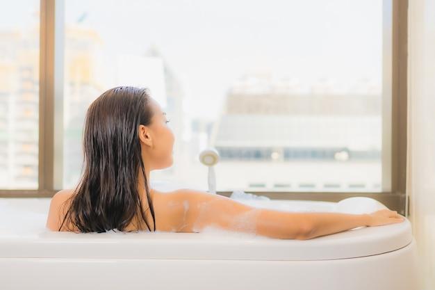 Portret pięknej młodej kobiety azjatyckie relaks cieszyć się kąpiel w wannie we wnętrzu łazienki