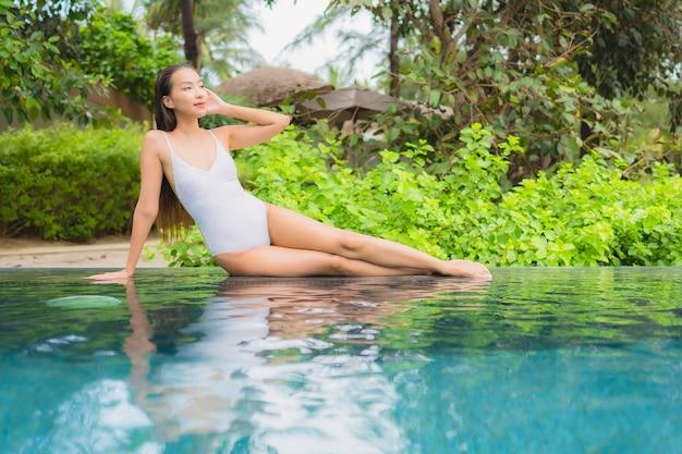 Portret pięknej młodej kobiety azjatyckie relaks przy odkrytym basenie w hotelowym kurorcie blisko morza