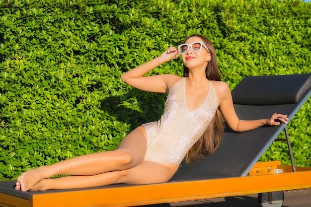 Portret pięknej młodej kobiety azjatyckie relaks przy odkrytym basenie w hotelowym kurorcie
