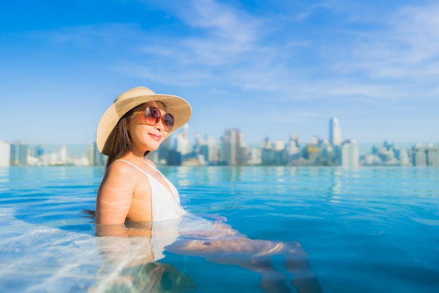 Portret pięknej młodej kobiety azjatyckie relaks przy odkrytym basenie z widokiem na miasto