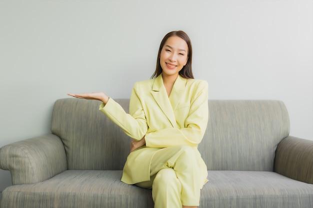 Portret pięknej młodej kobiety azjatyckie siedzieć z uśmiechem na kanapie we wnętrzu salonu
