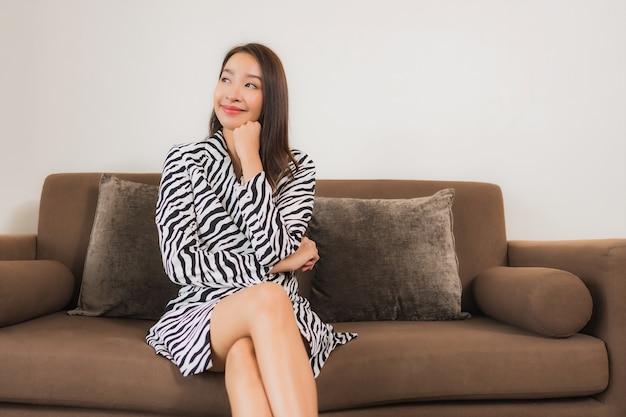 Portret pięknej młodej kobiety azjatyckie uśmiech zrelaksować się na kanapie we wnętrzu salonu