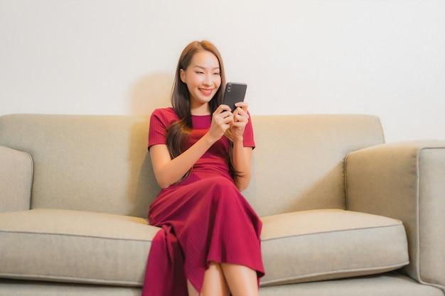 Portret pięknej młodej kobiety azjatyckie za pomocą inteligentnego telefonu komórkowego na kanapie we wnętrzu salonu