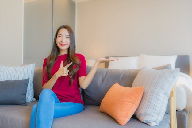 Portret pięknej młodej kobiety azjatyckie zrelaksować się uśmiech na kanapie w salonie