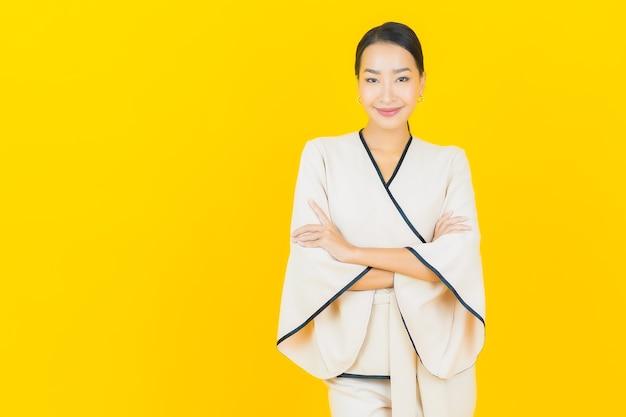 Portret pięknej młodej kobiety azjatyckiego biznesu uśmiechając się z białym garniturem na żółtej ścianie