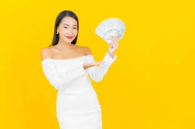 Portret pięknej młodej kobiety azjatyckiego biznesu z dużą ilością gotówki na żółtej ścianie