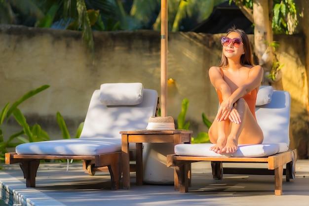 Portret pięknej młodej kobiety azjatyckiej cieszyć się relaksem przy basenie na wakacje