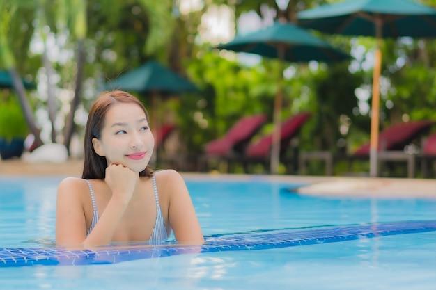 Portret pięknej młodej kobiety azjatyckiej cieszyć się relaksujący uśmiech wypoczynek wokół odkrytego basenu w hotelu