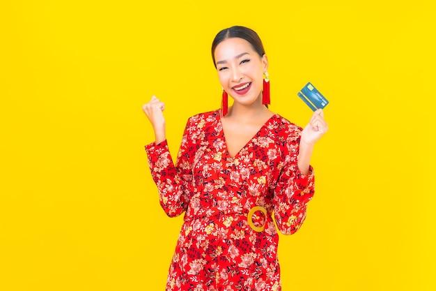 Portret pięknej młodej kobiety azjatyckiej karty kredytowej na zakupy na żółtej ścianie na białym tle