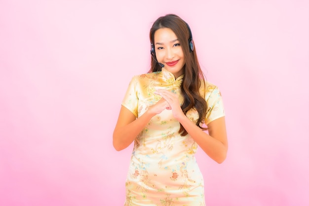 Portret pięknej młodej kobiety azjatyckiej klient call center opieki na różowej ścianie koloru