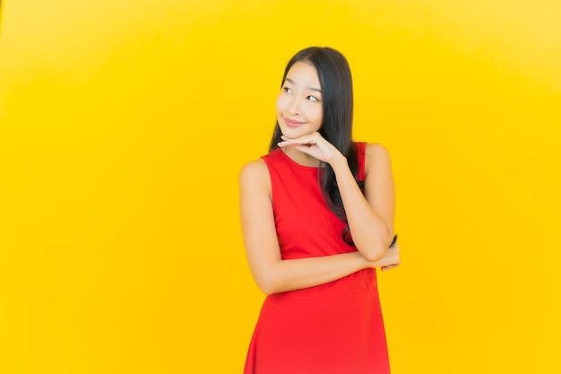 Portret pięknej młodej kobiety azjatyckiej nosić czerwoną sukienkę uśmiech z działaniem na żółtej ścianie