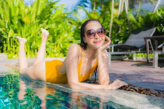 Portret pięknej młodej kobiety azjatyckiej relaks szczęśliwy uśmiech wokół odkrytego basenu w hotelowym kurorcie na wakacje