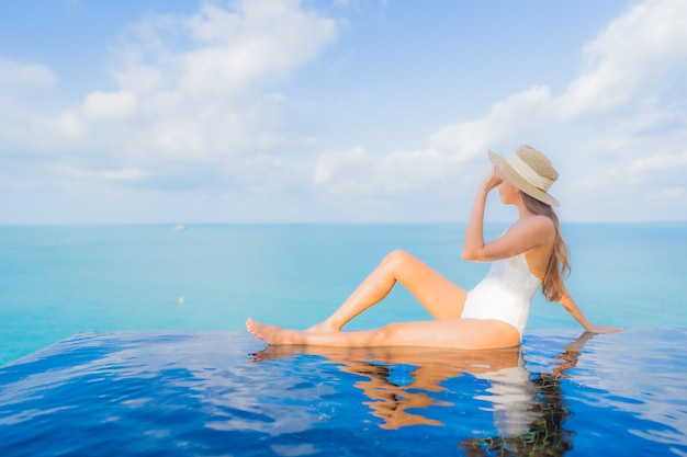 Portret pięknej młodej kobiety azjatyckiej relaks uśmiech wypoczynek wokół odkrytego basenu w hotelowym kurorcie na wakacje w podróży
