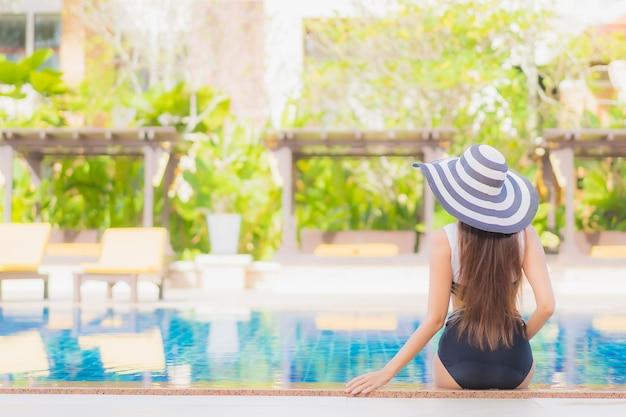 Portret pięknej młodej kobiety azjatyckiej relaks uśmiech wypoczynek wokół odkrytego basenu w hotelowym kurorcie na wakacje