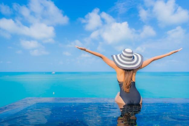 Portret pięknej młodej kobiety azjatyckiej relaks uśmiech wypoczynek wokół odkrytego basenu w hotelu z widokiem na morze