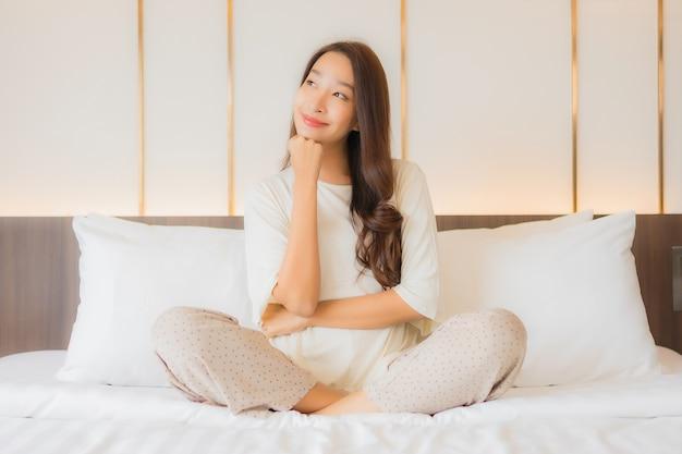 Portret pięknej młodej kobiety azjatyckiej uśmiech relaks relaks na łóżku we wnętrzu sypialni