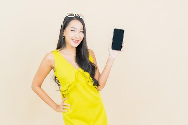 Portret pięknej młodej kobiety azjatyckiej uśmiech z inteligentny telefon komórkowy na kolorowej ścianie