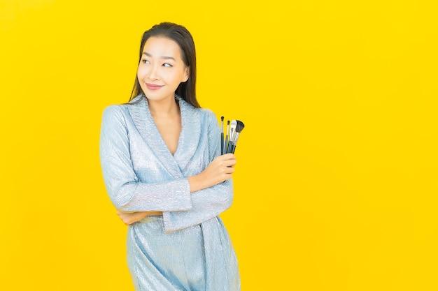 Portret pięknej młodej kobiety azjatyckiej uśmiech z kosmetycznym pędzlem do makijażu na żółtej ścianie