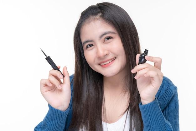Portret pięknej młodej kobiety azjatyckiej vlogger urody trzymaj kosmetyki na sprzedaż online