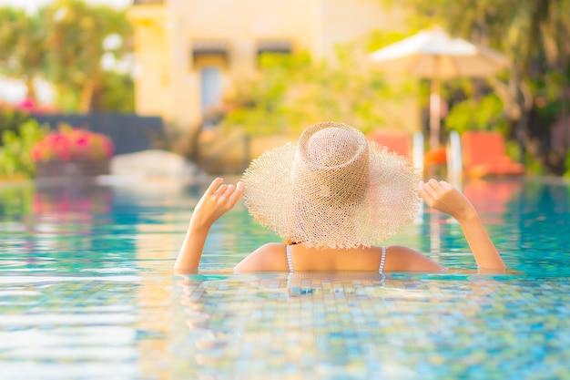Portret pięknej młodej kobiety azjatyckiej zrelaksować się uśmiech cieszyć się wypoczynkiem przy basenie w hotelu wypoczynkowym na wakacjach