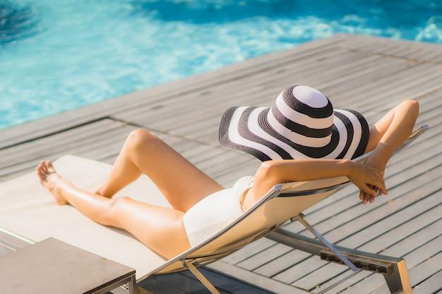 Portret pięknej młodej kobiety azjatykci szczęśliwy uśmiech i relaksuje wokoło pływackiego basenu w hotelowym kurorcie
