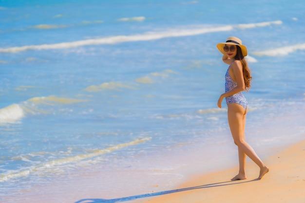Portret pięknej młodej kobiety azjatykci szczęśliwy uśmiech relaksuje na tropikalnym plażowym dennym oceanie dla czas wolny podróży