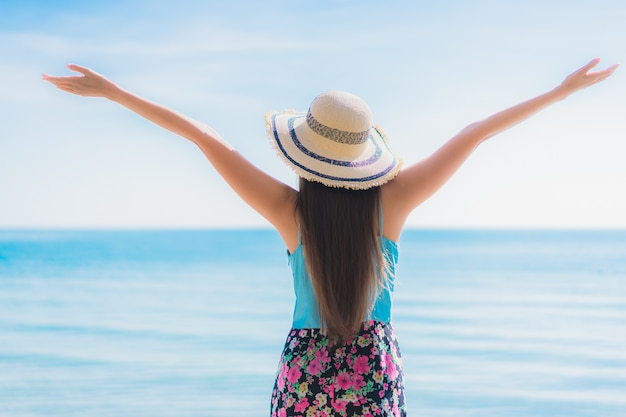 Portret pięknej młodej kobiety azjatykci szczęśliwy uśmiech relaksuje wokoło plażowego oceanu i morza
