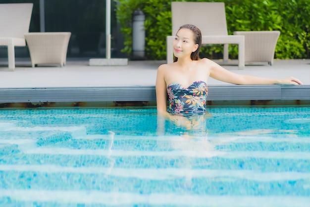 Portret pięknej młodej kobiety azji relaksuje na basenie w hotelowym kurorcie