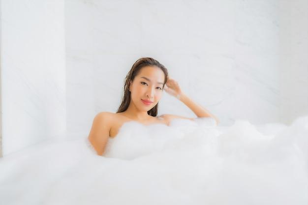 Portret pięknej młodej kobiety azji relaksuje w wannie